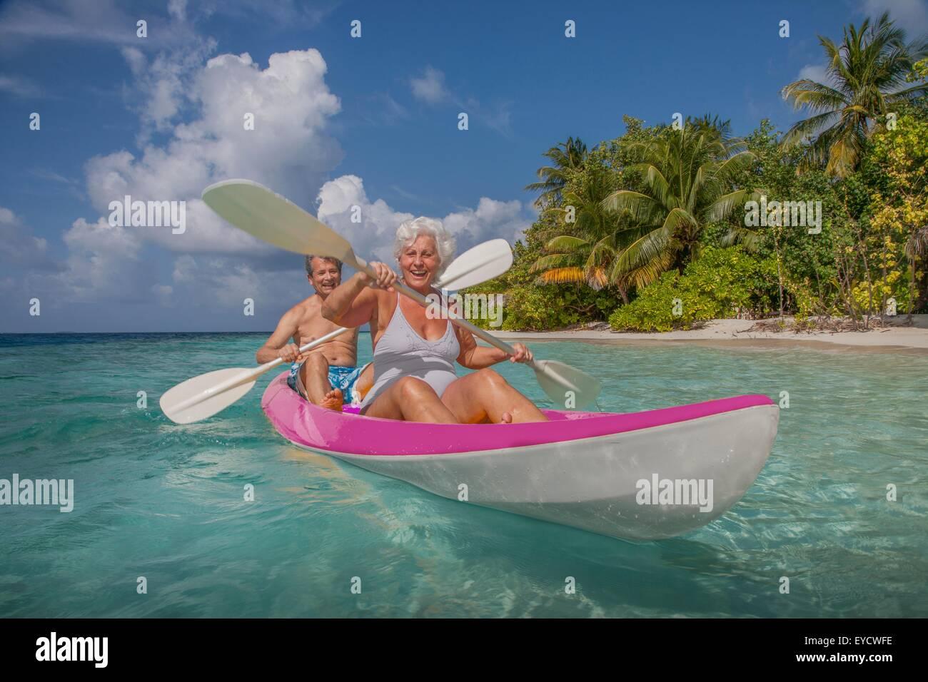 Senior couple in canoe, Maldives - Stock Image