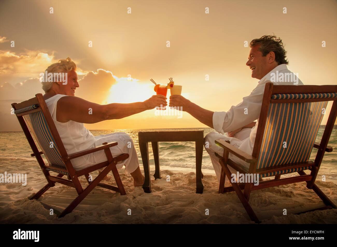 Senior couple toasting drinks on beach, Maldives - Stock Image