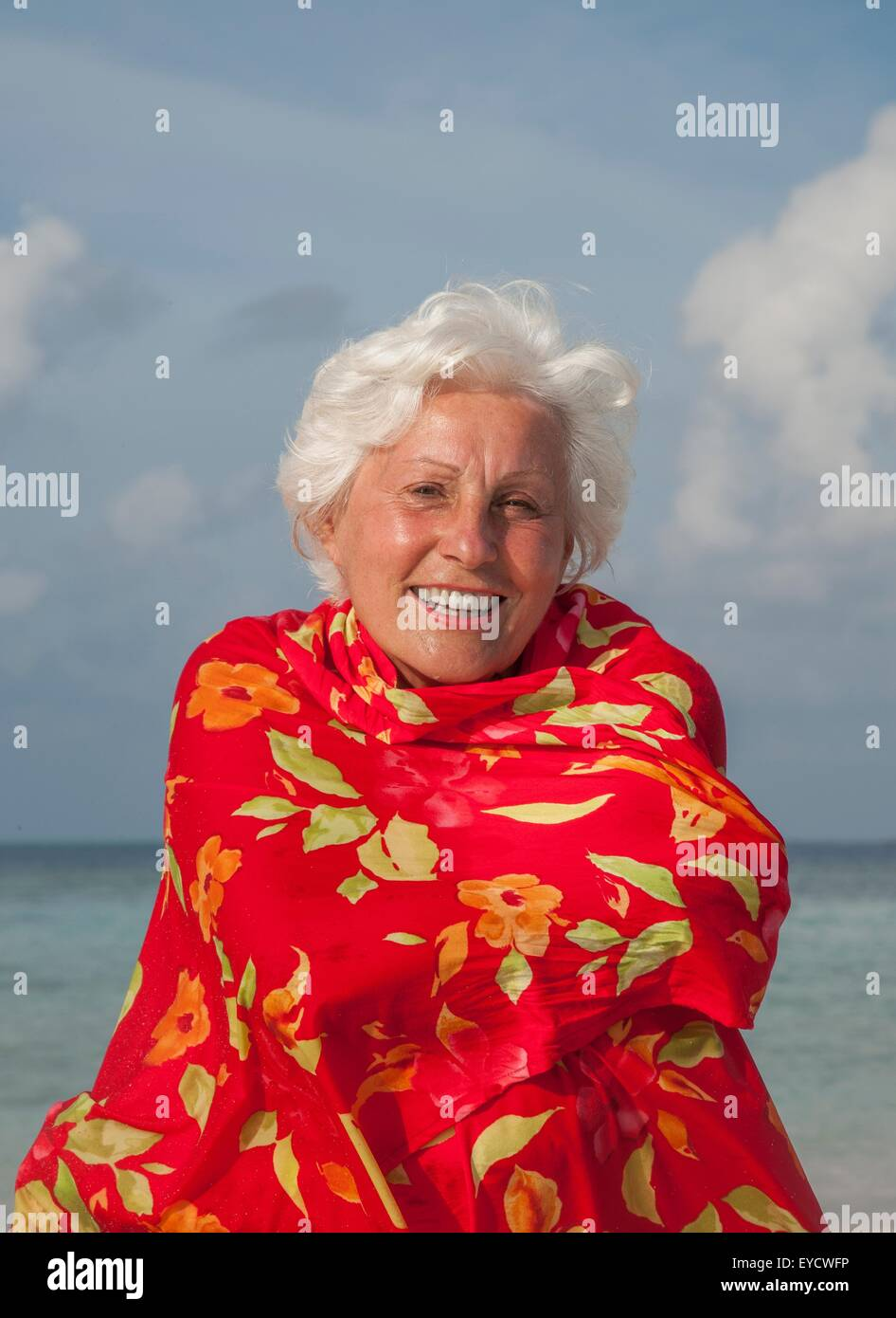 Senior woman wrapped in shawl, portrait - Stock Image