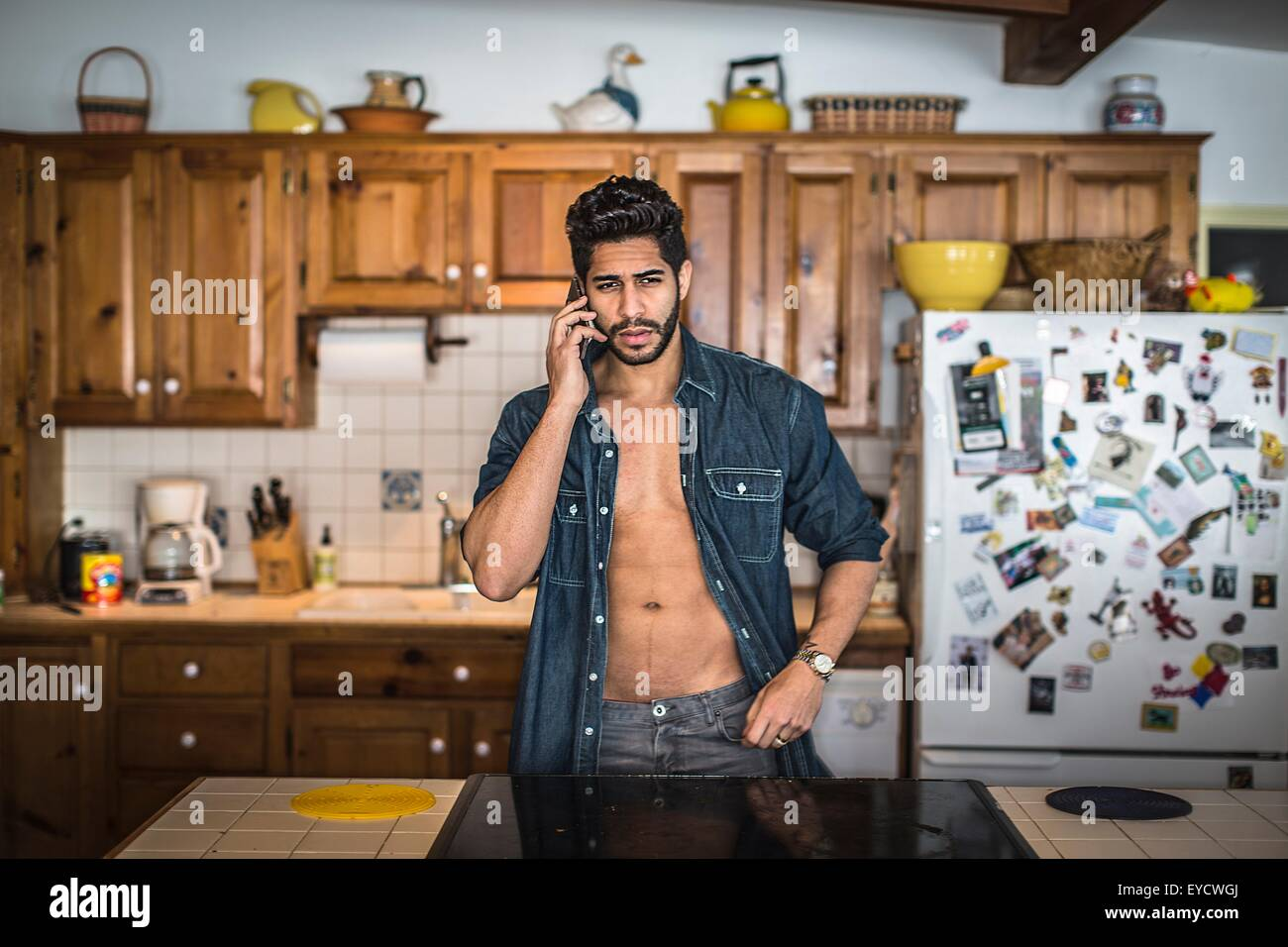 Young man on cell phone in kitchen Stock Photo