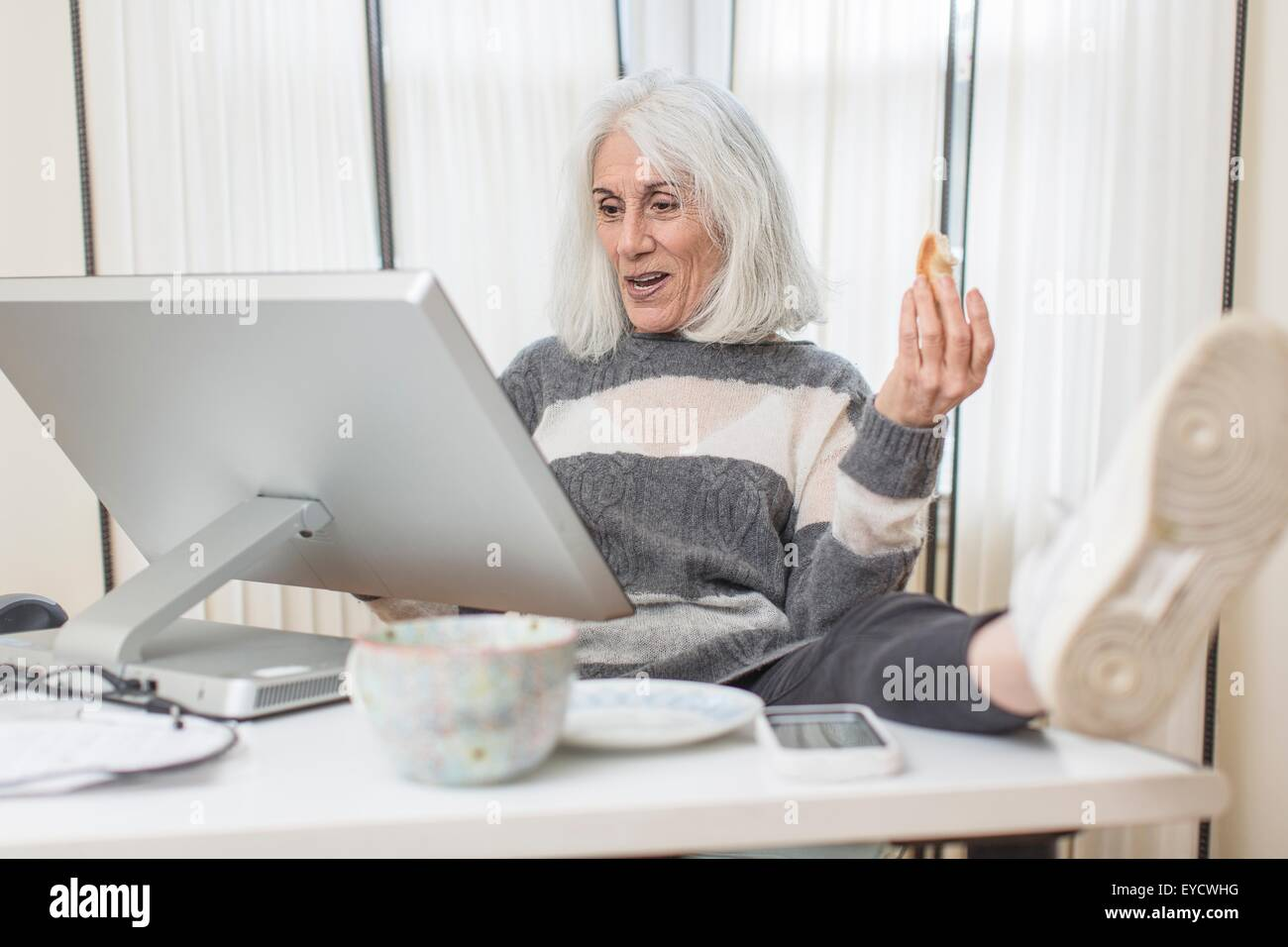 Portrait of senior woman sitting at computer with foot on desk - Stock Image