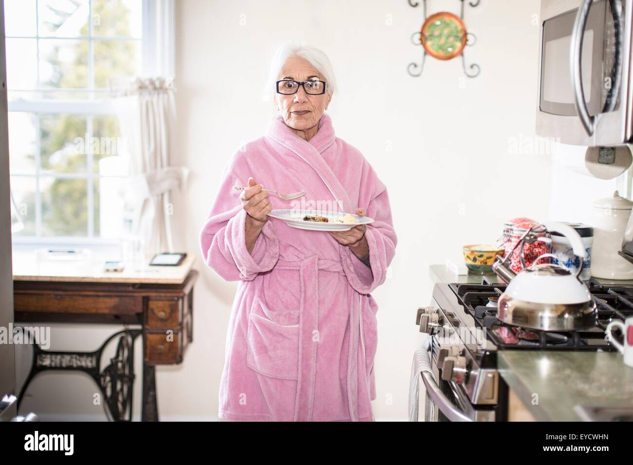 Senior woman standing in kitchen holding plate of food - Stock Image