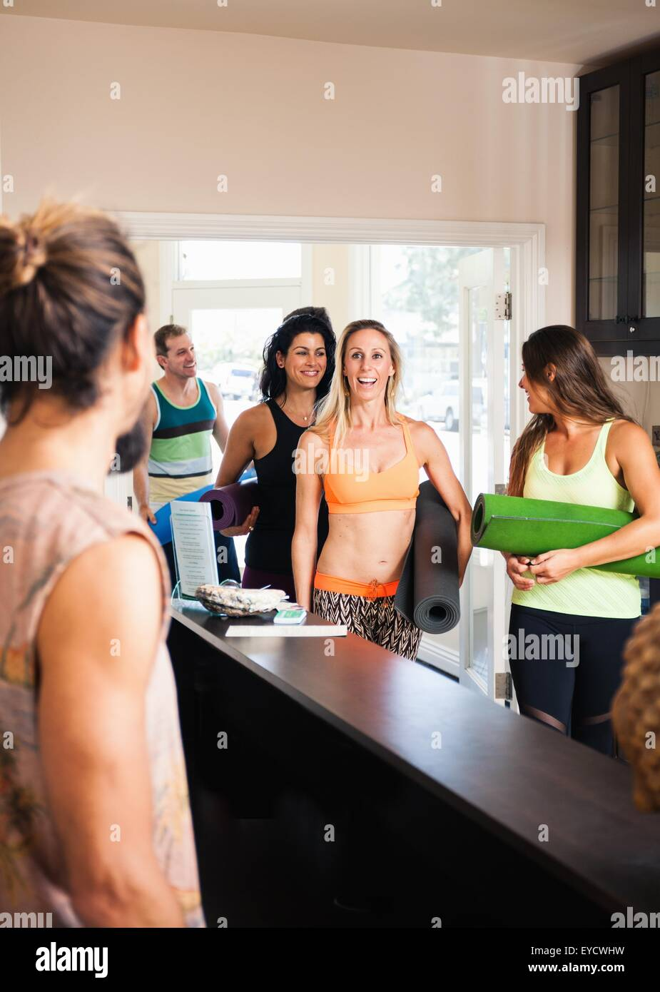 Mid adult woman arriving at yoga class - Stock Image