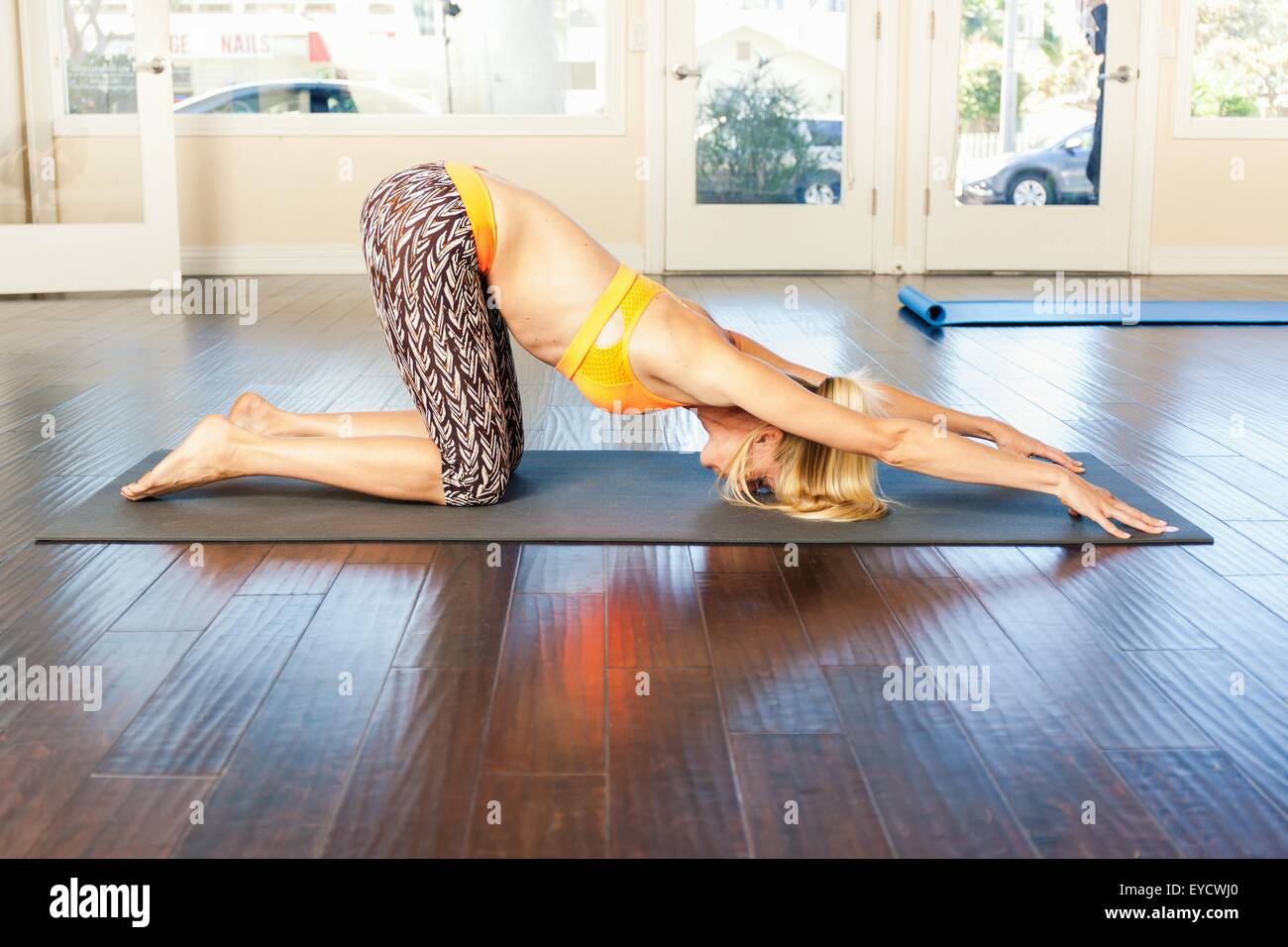 Mid adult woman in yoga pose - Stock Image