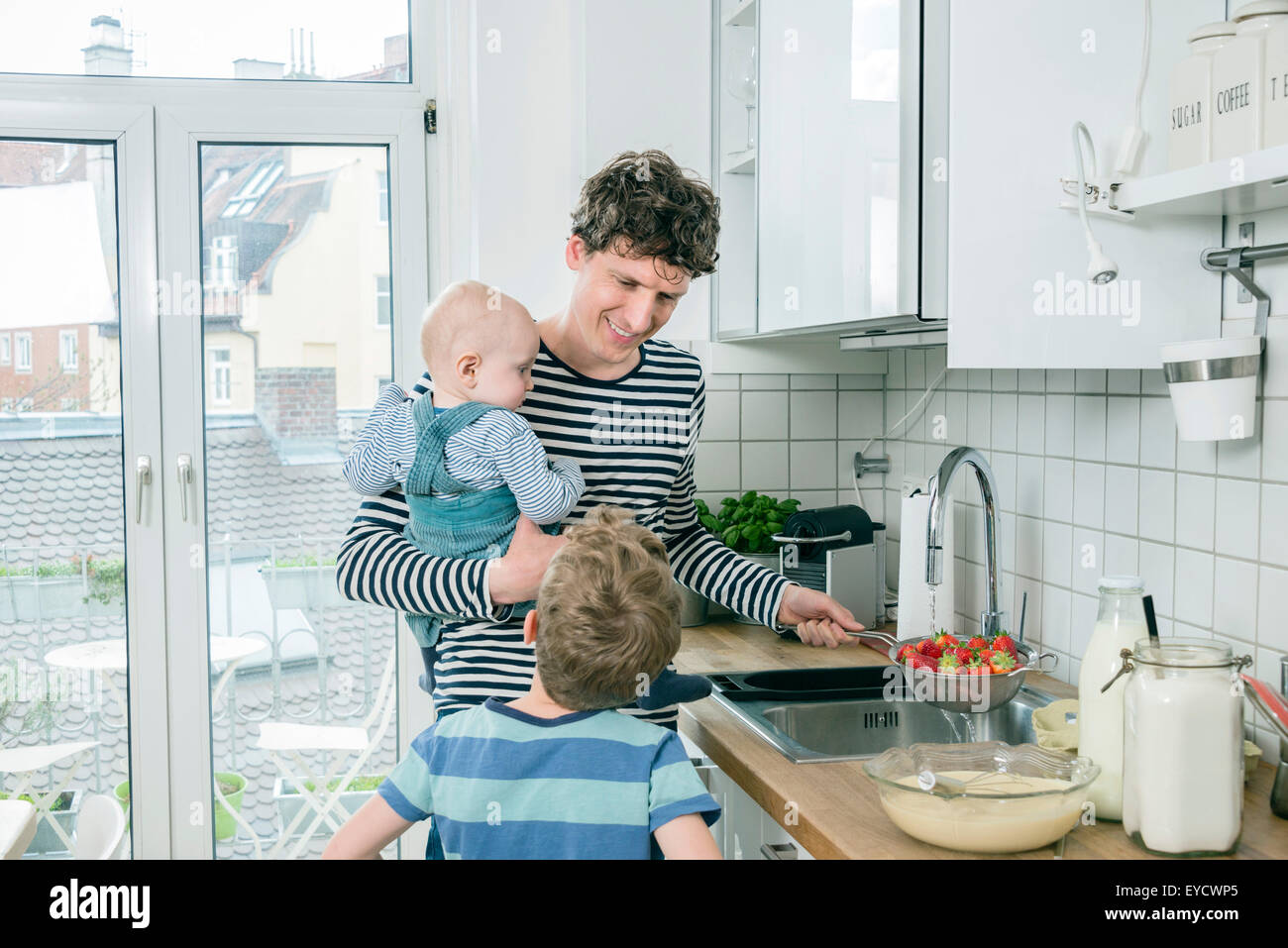 Father prepares food while holding baby in kitchen - Stock Image