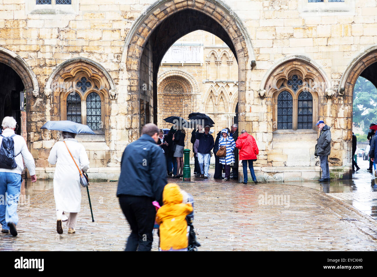 Sheltering under umbrellas in rain rainy day bad weather shelter under arch Lincoln city UK England Lincolnshire - Stock Image
