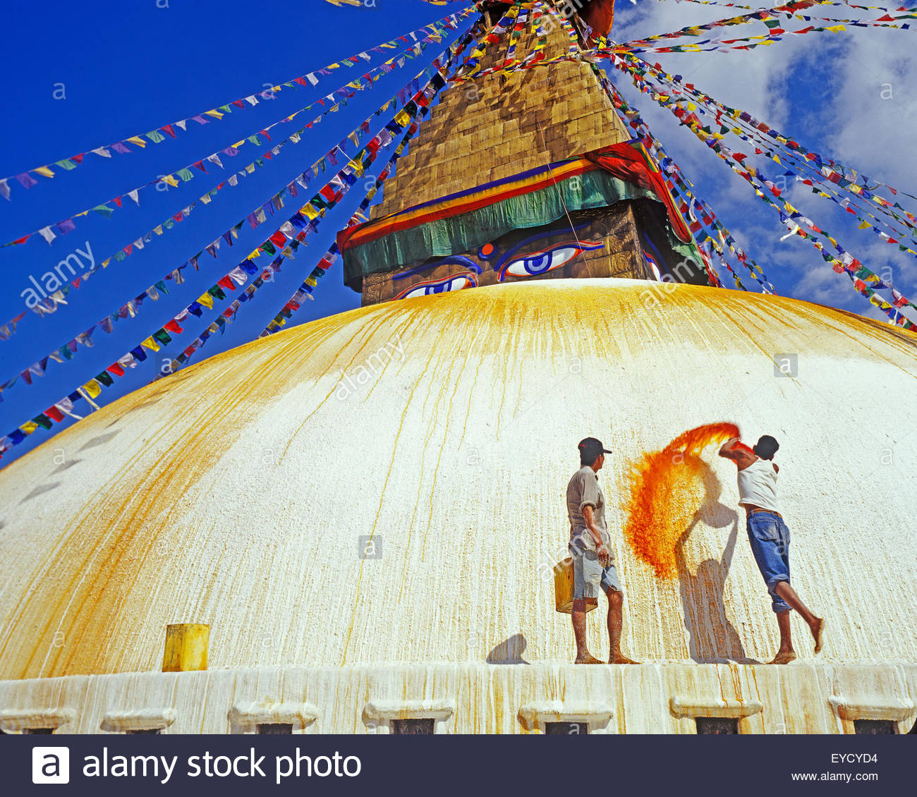Young man throwing saffron water on Boudhanath Stupa, Boudhanath, Katmandu, Nepal, Asia - Stock Image