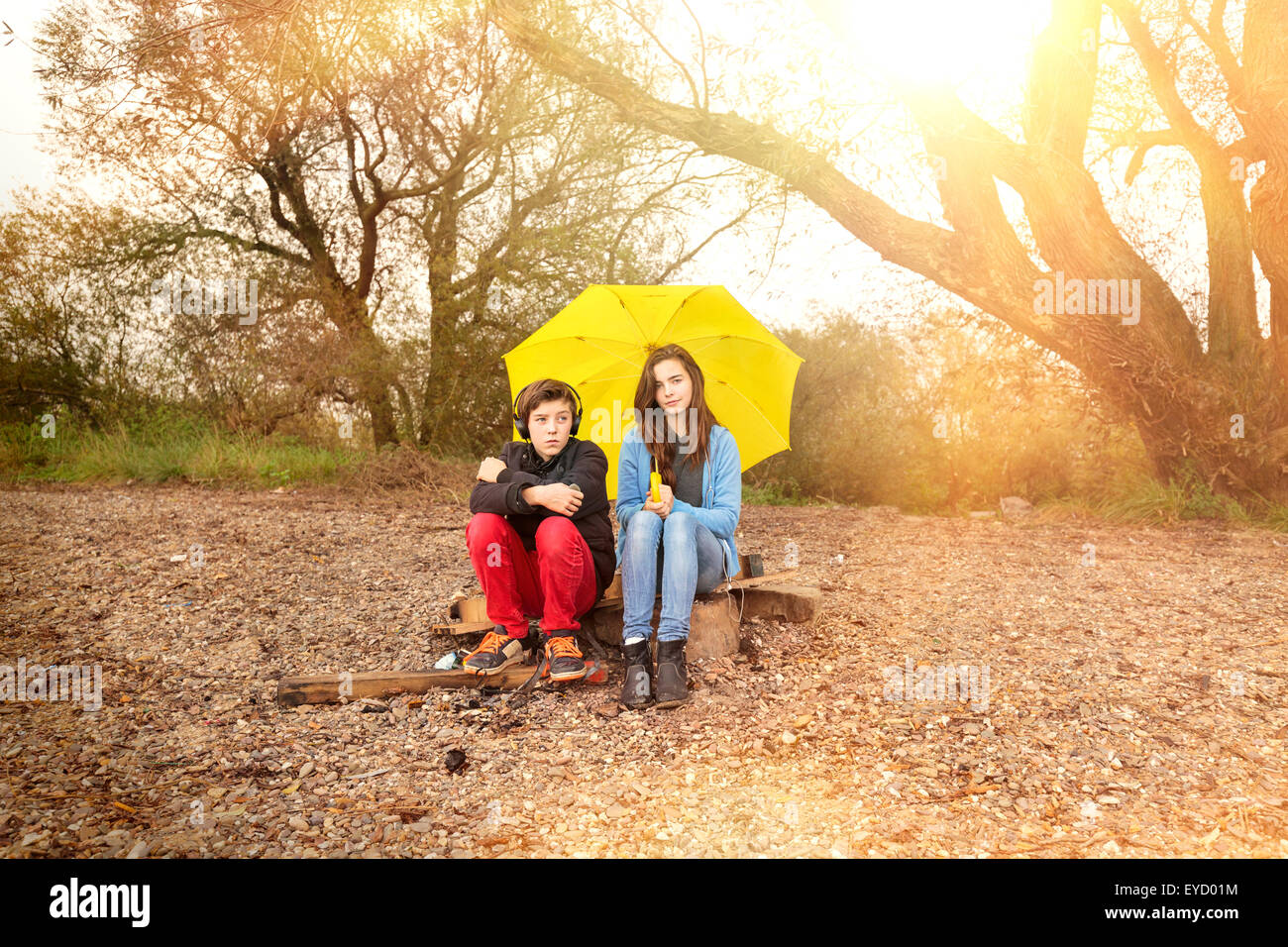 two teenager with umbrella sitting on a dirty beach with sun in background - Stock Image