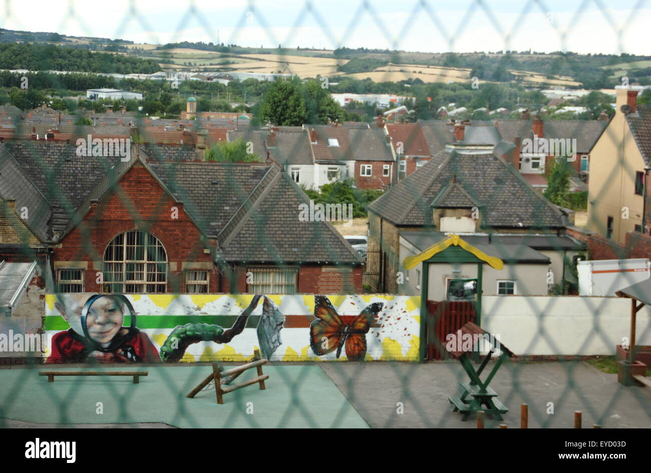 A children's play area seen through fencing in Rotherham looking to the Eastwood area of the town, South Yorkshire - Stock Image