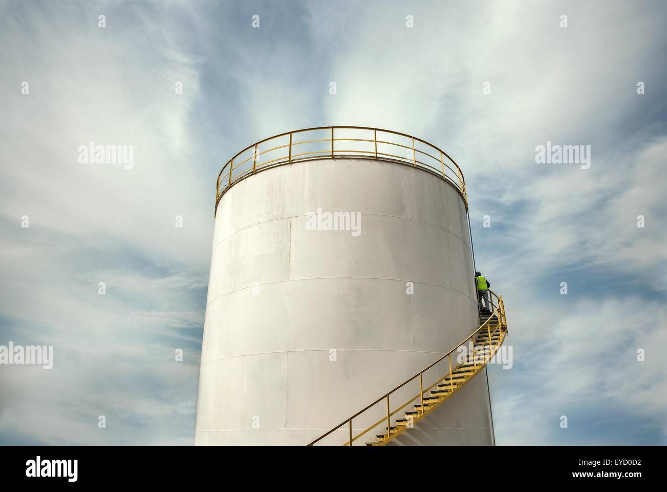 Industrial worker climbing stairs on oil storage tank - Stock Image