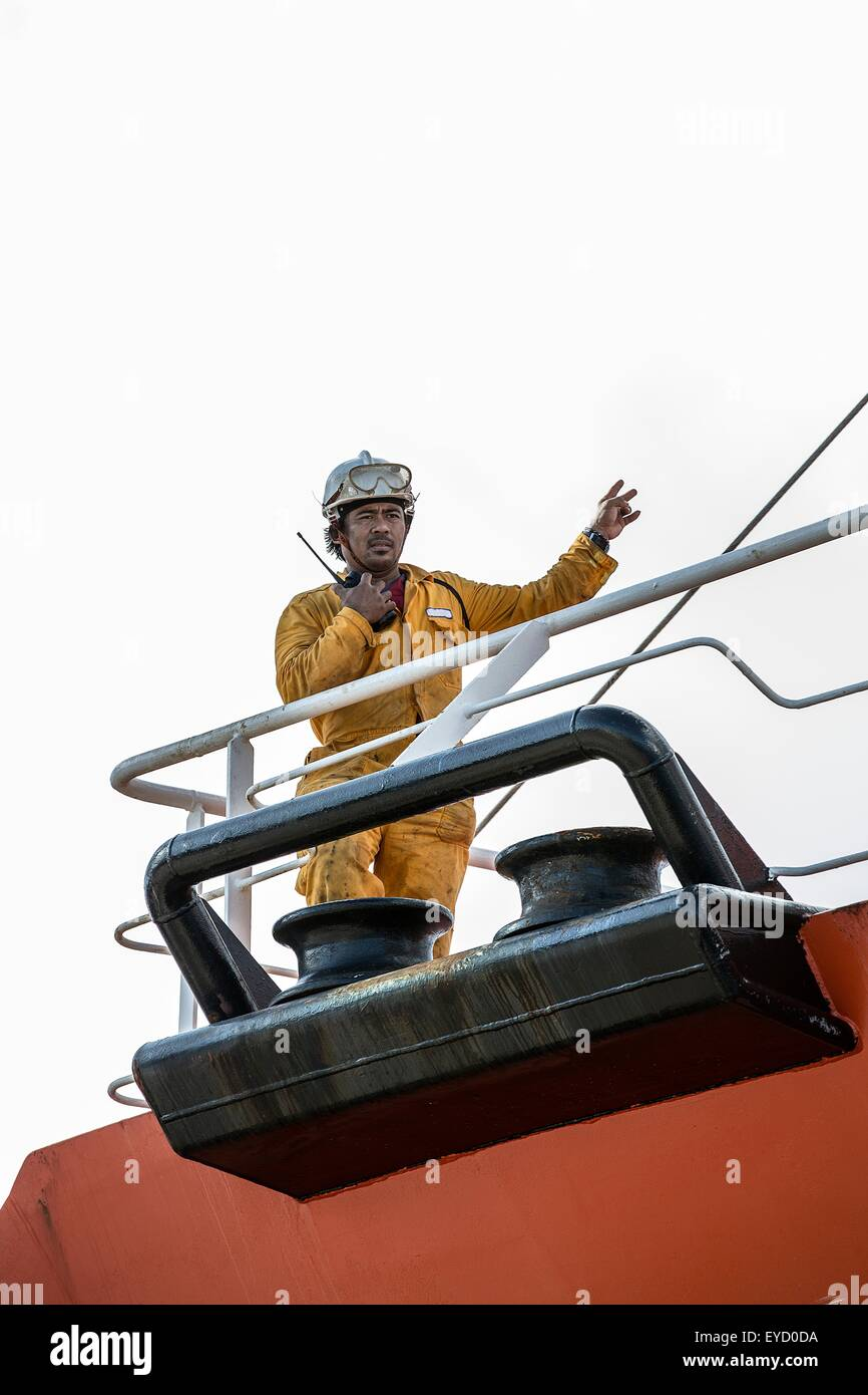 Worker using walkie talkie on oil tanker deck - Stock Image