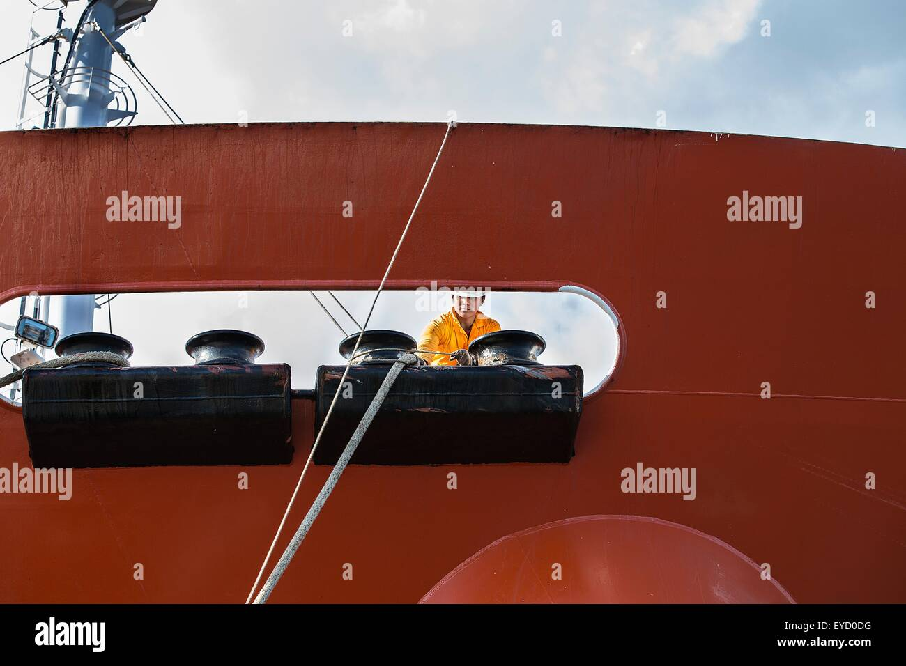 Worker fastening ropes to mooring posts on oil tanker deck - Stock Image