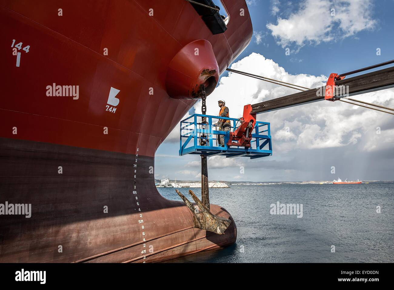 Worker on viewing platform inspecting oil tanker - Stock Image