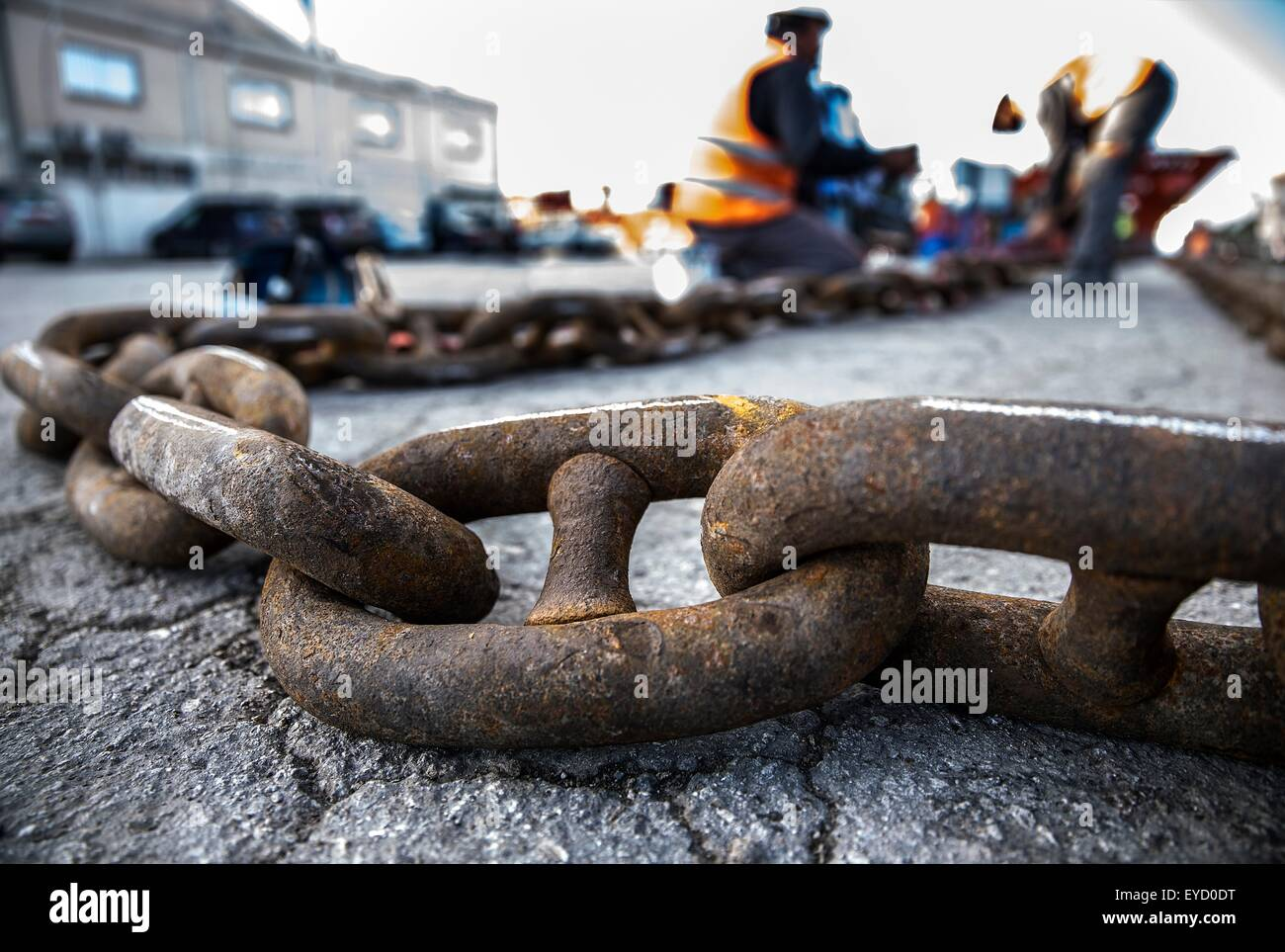 Surface level view on welders welding chain on dock - Stock Image