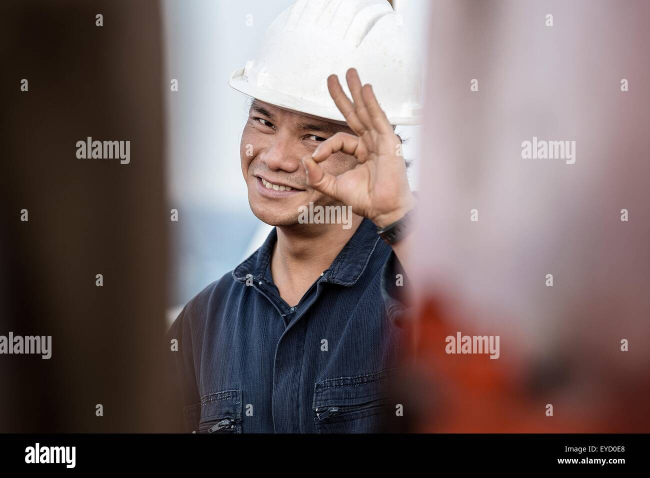 Portrait of worker on oil tanker making ok gesture - Stock Image