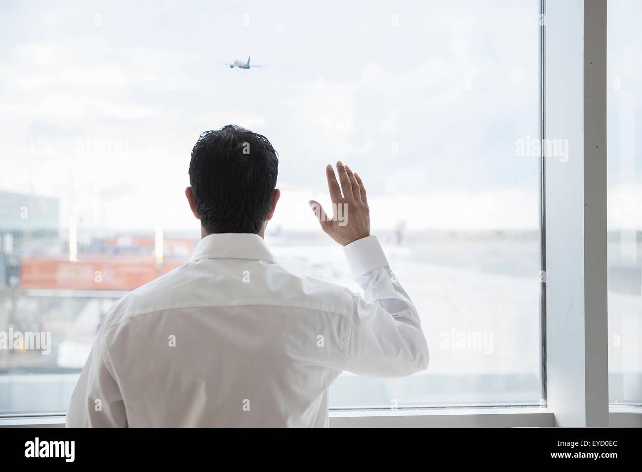 Rear view of dock harbormaster waving from control room - Stock Image