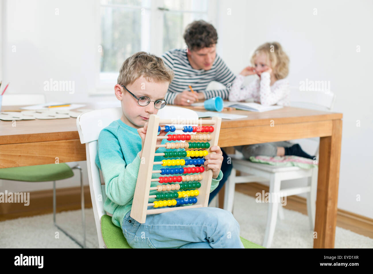 Father and children calculating with abacus - Stock Image