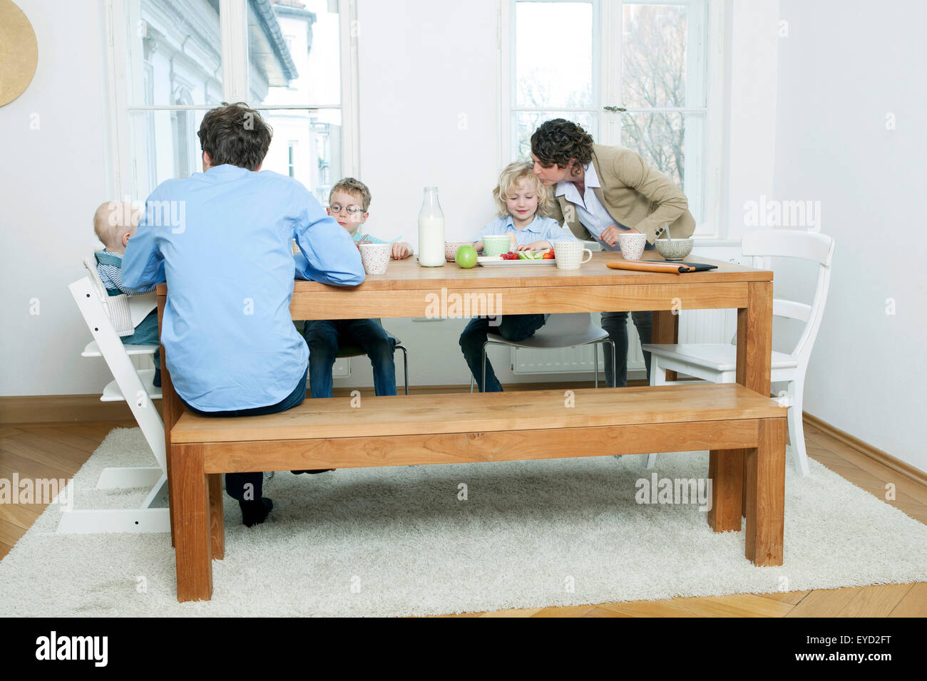 Family at breakfast table in kitchen - Stock Image