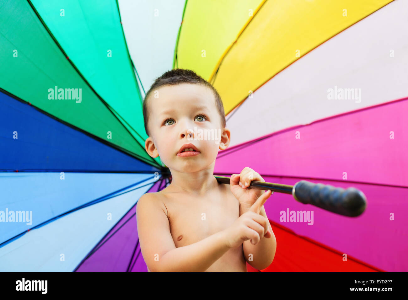 Adorable portrait of happy baby boy holding in hands and turning big umbrella with vibrant rainbow colors pattern. Stock Photo