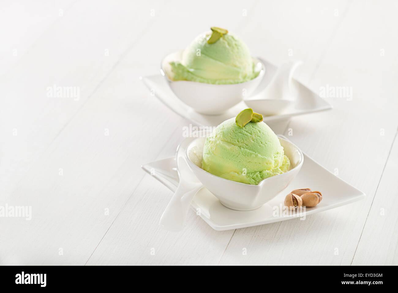Fresh pistachio ice cream in cup close up. - Stock Image