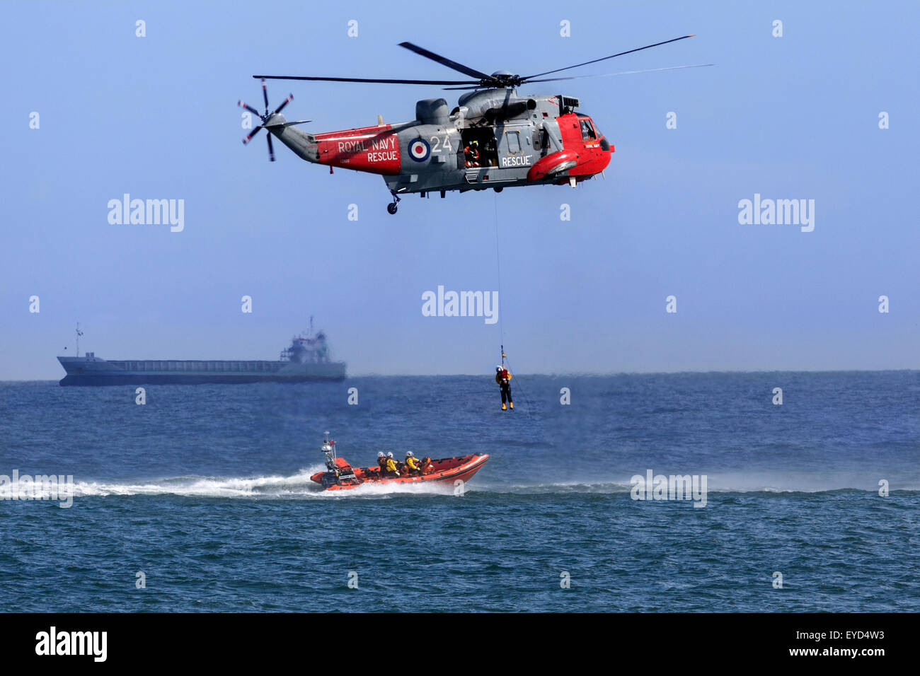A Royal Navy Sea King Search and Rescue helicopter lifting a casualty from a small boat in a busy shipping lane. - Stock Image