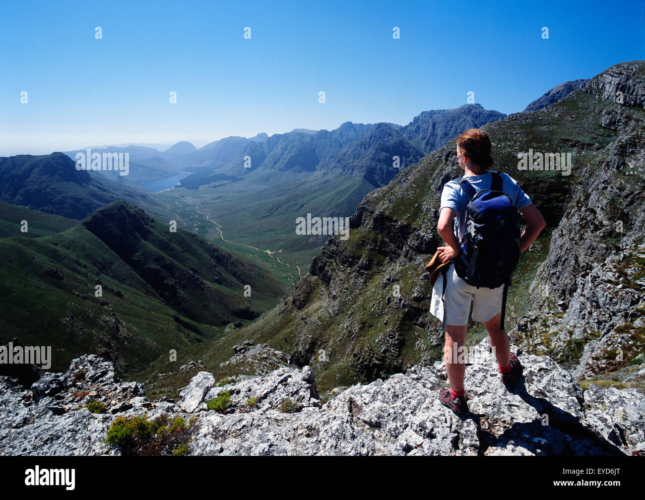 A Man With A Backpack Stands On A Mountain Ridge Looking Out Over The Valley And Range - Stock Image