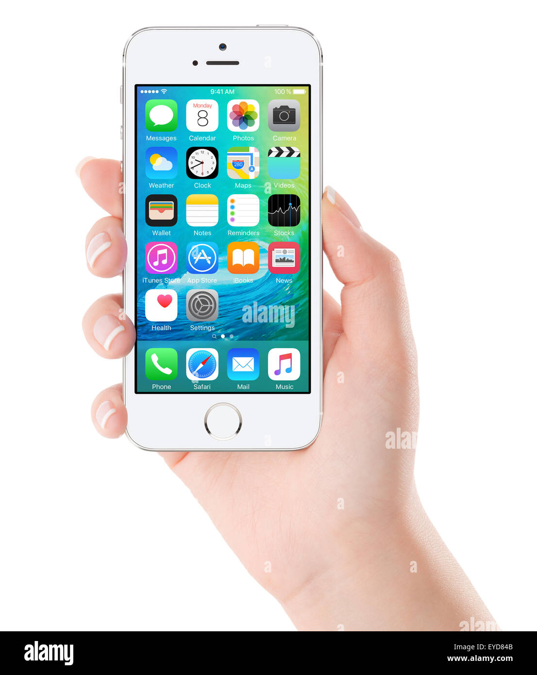 Varna, Bulgaria - February 02, 2015: iOS 9 homescreen on white Apple iPhone display in female hand. Isolated white - Stock Image