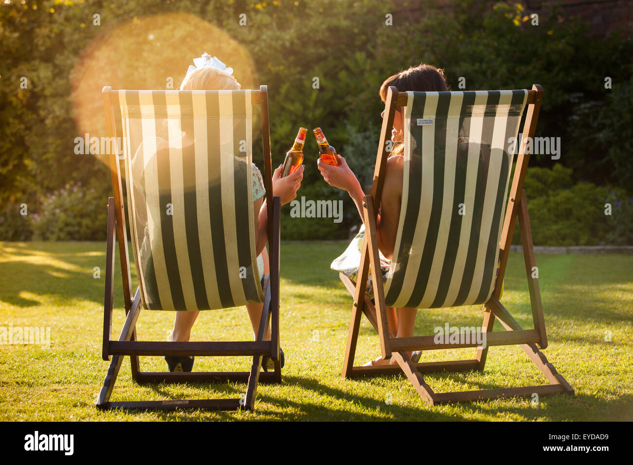 Two women sitting in deck chairs against the late afternoon summer sun, drinking bottled beers. - Stock Image
