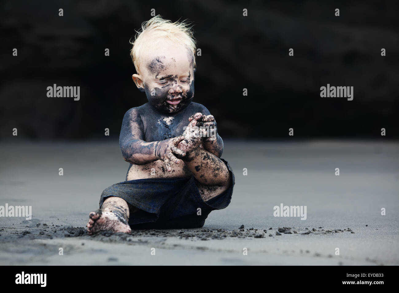 Funny portrait of smiling child with dirty face sitting and playing with fun on black sand sea beach before swimming - Stock Image