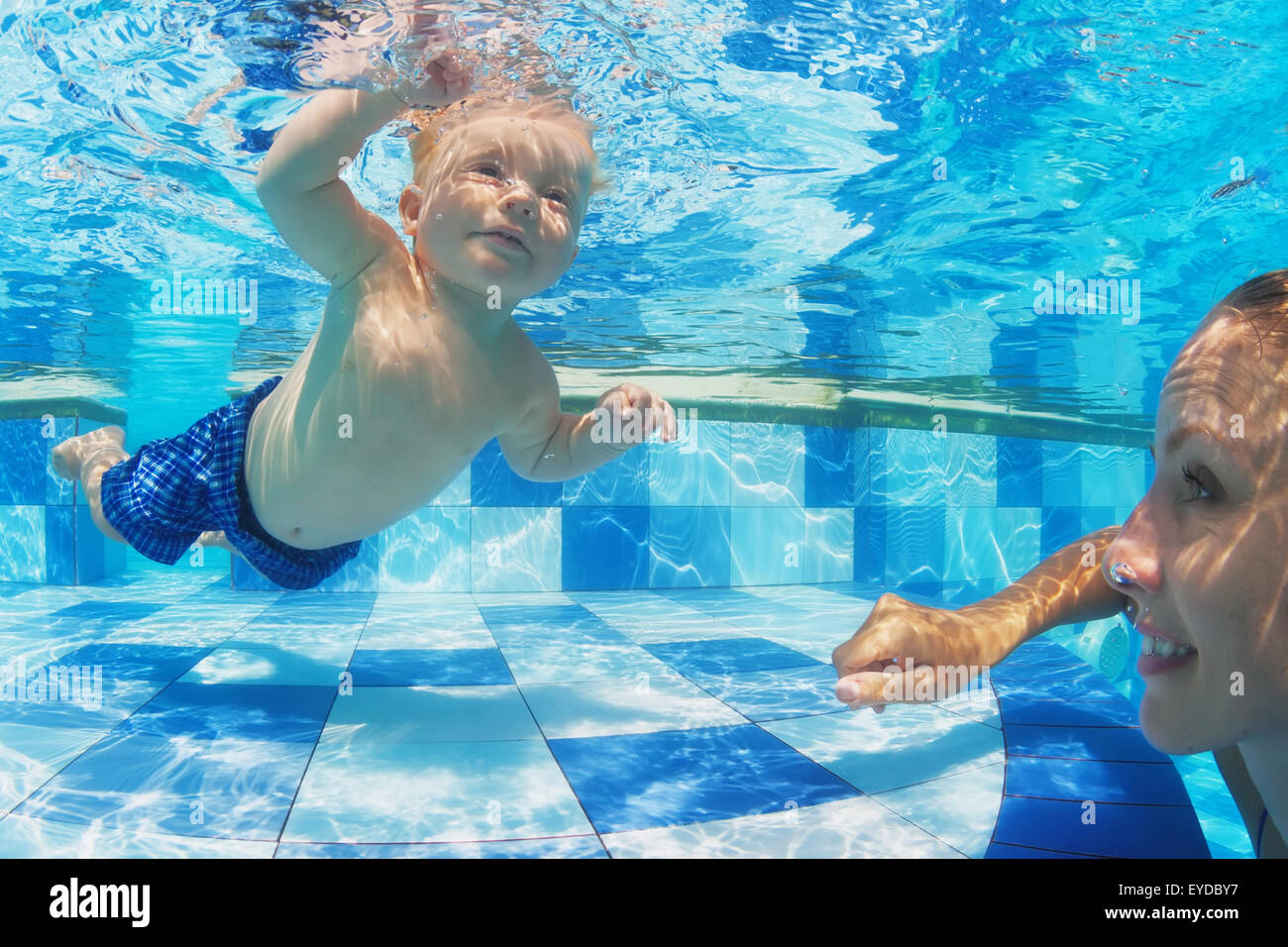 Portrait of child swimming with fun underwater in pool with diving cheerful mother. Stock Photo