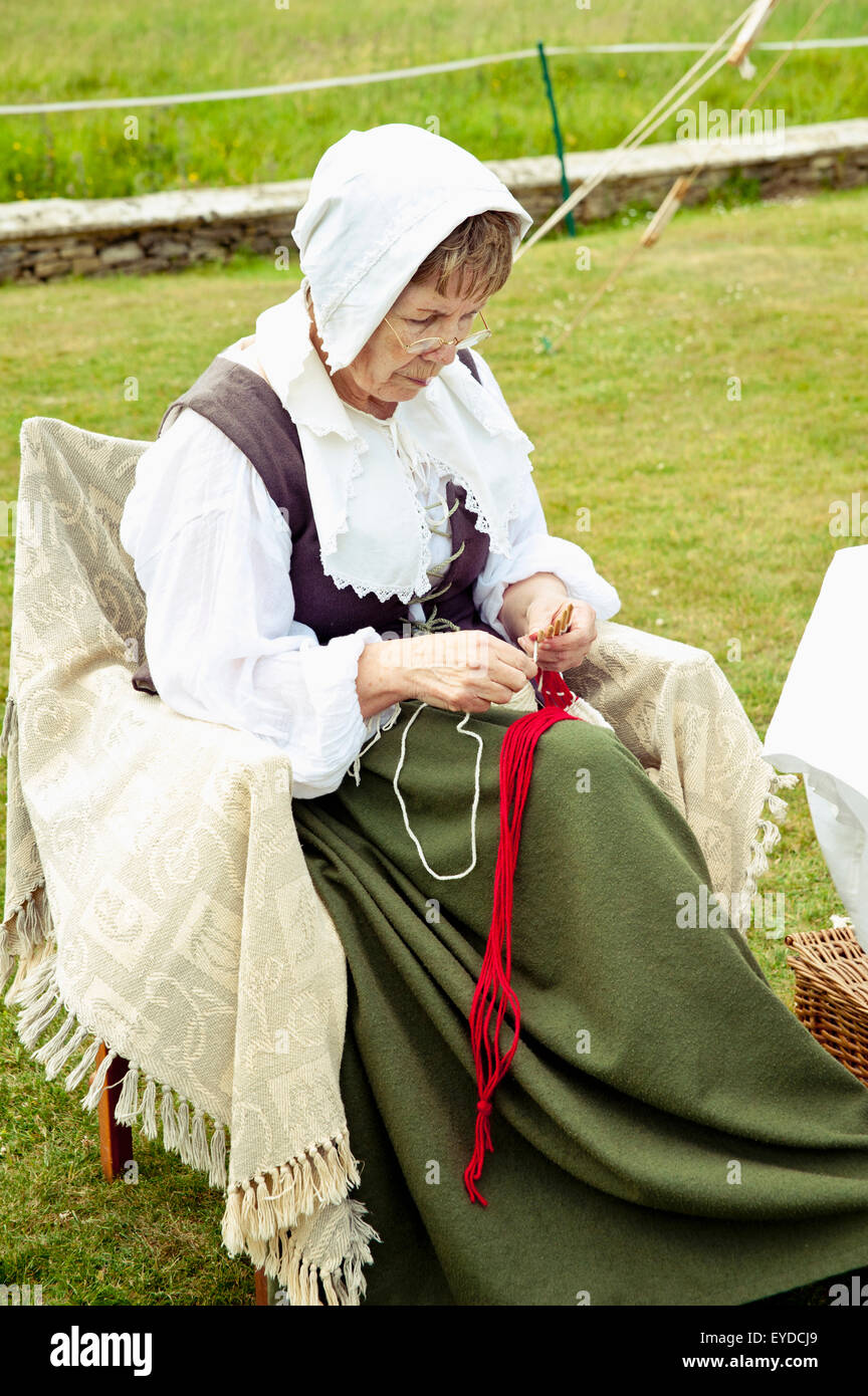 Senior Female Weaving While Sitting On Chair In Front Of Lacock Abbey, Lacock, Wiltshire, Uk - Stock Image