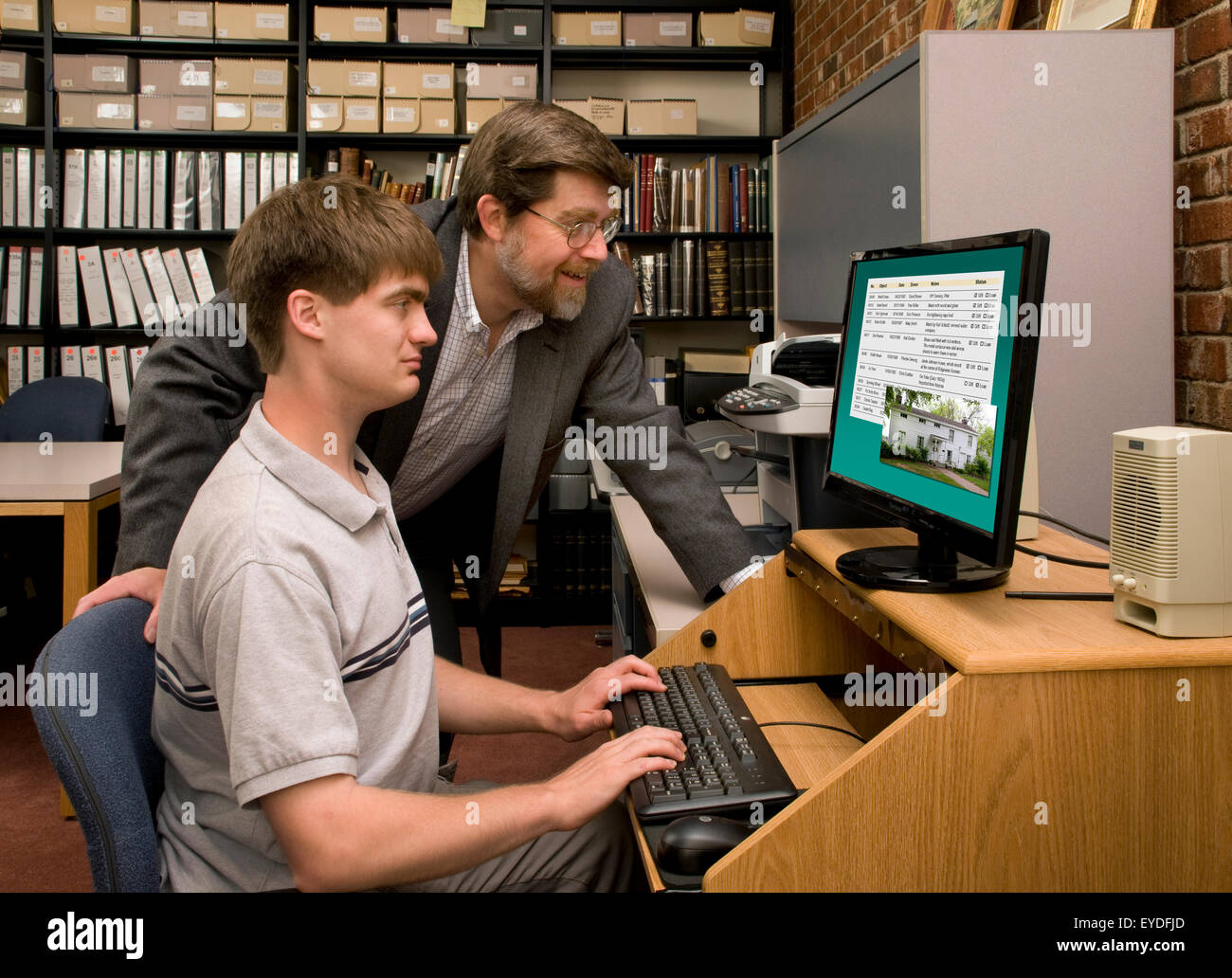 Teacher or mentor guiding a student in a database search in an archive or library room - Stock Image