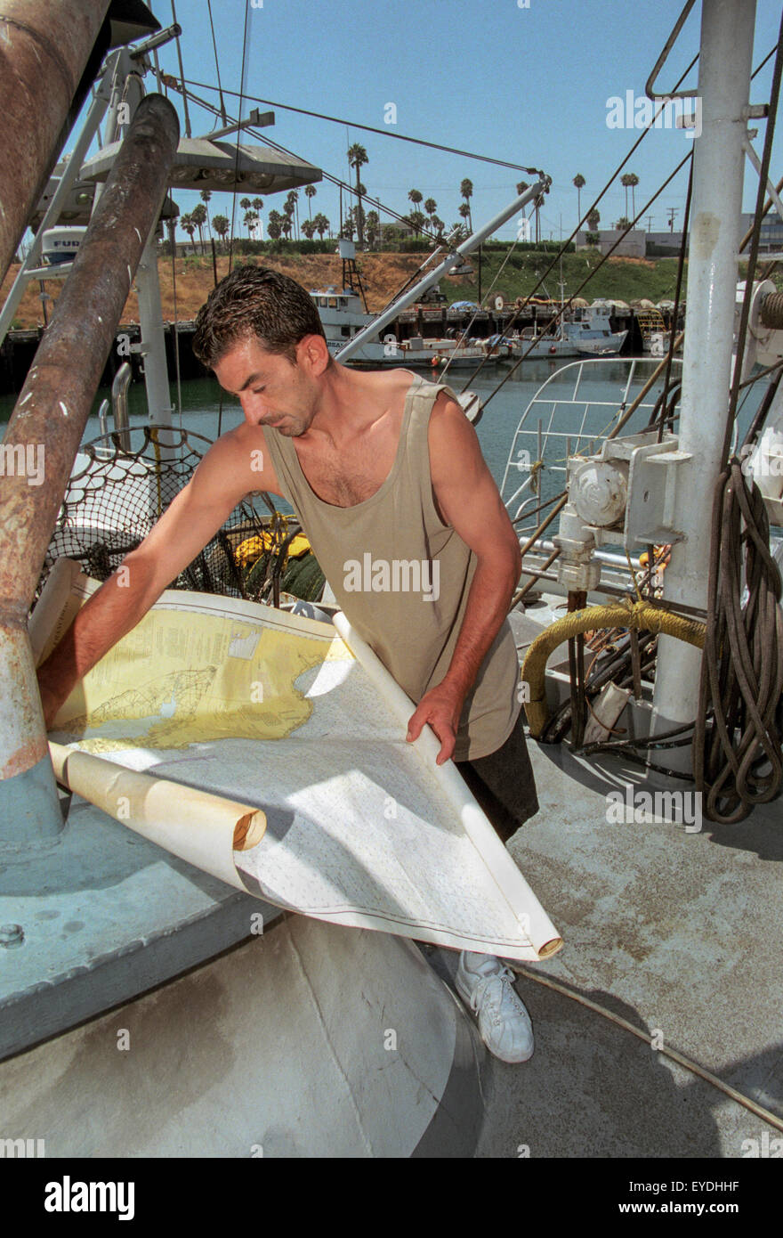 Before casting off from San Pedro, CA, a fisherman checks his navigation chart. - Stock Image