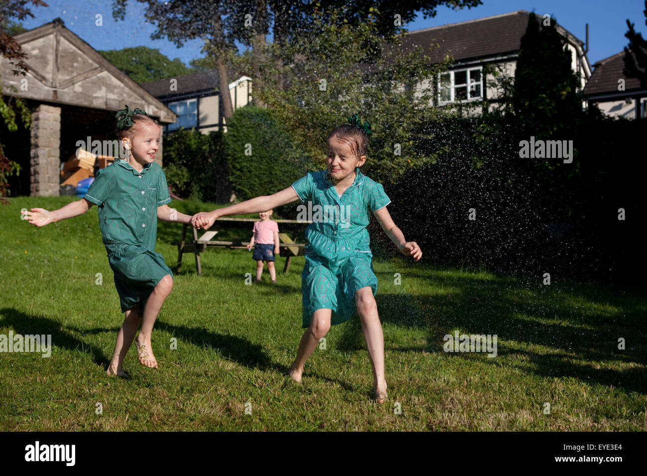 Two children in school dresses running through a water sprinkler. - Stock Image