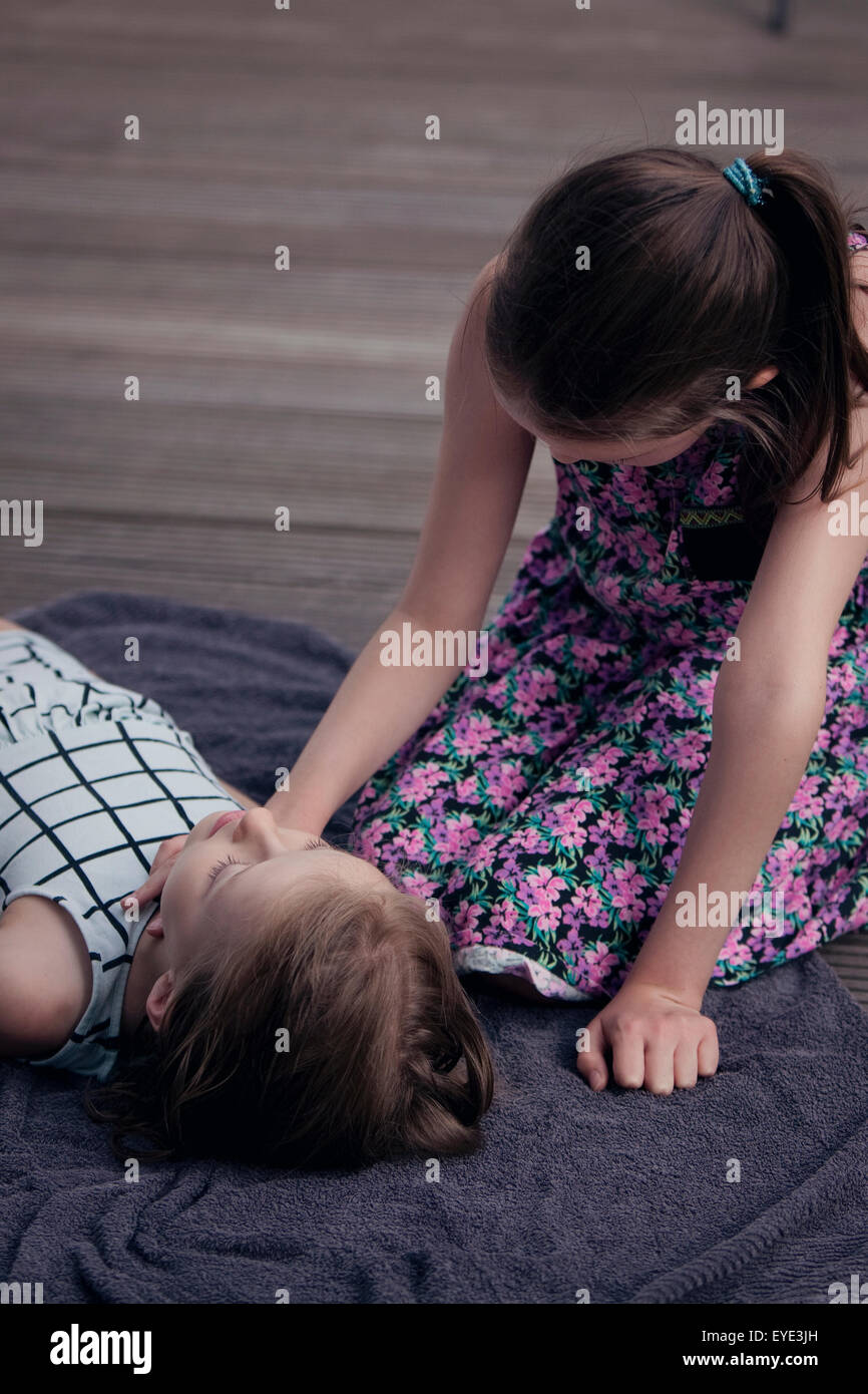 Child practising first aid CPR and checking the pulse on another child. - Stock Image