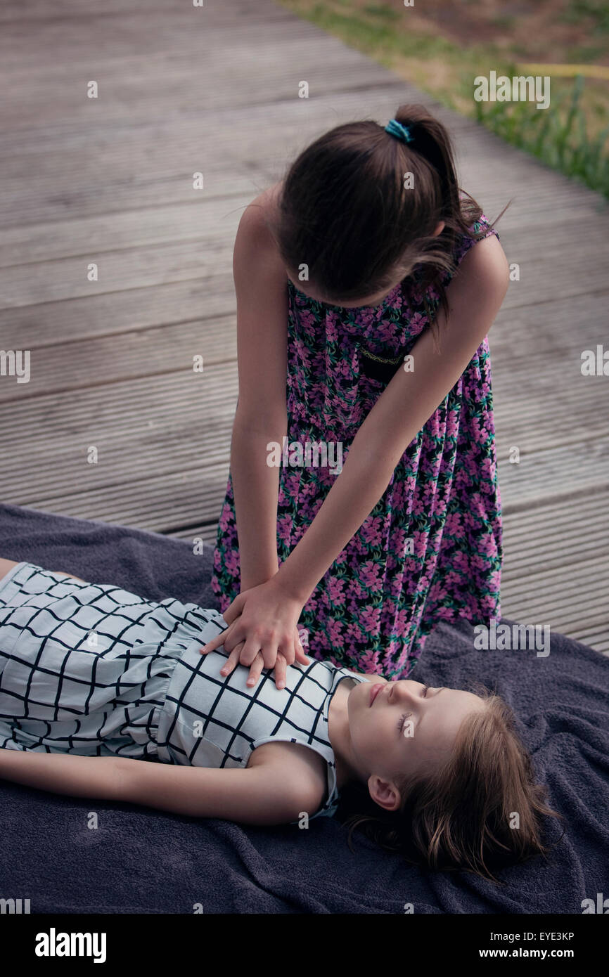 Child practising first aid CPR on another child. - Stock Image