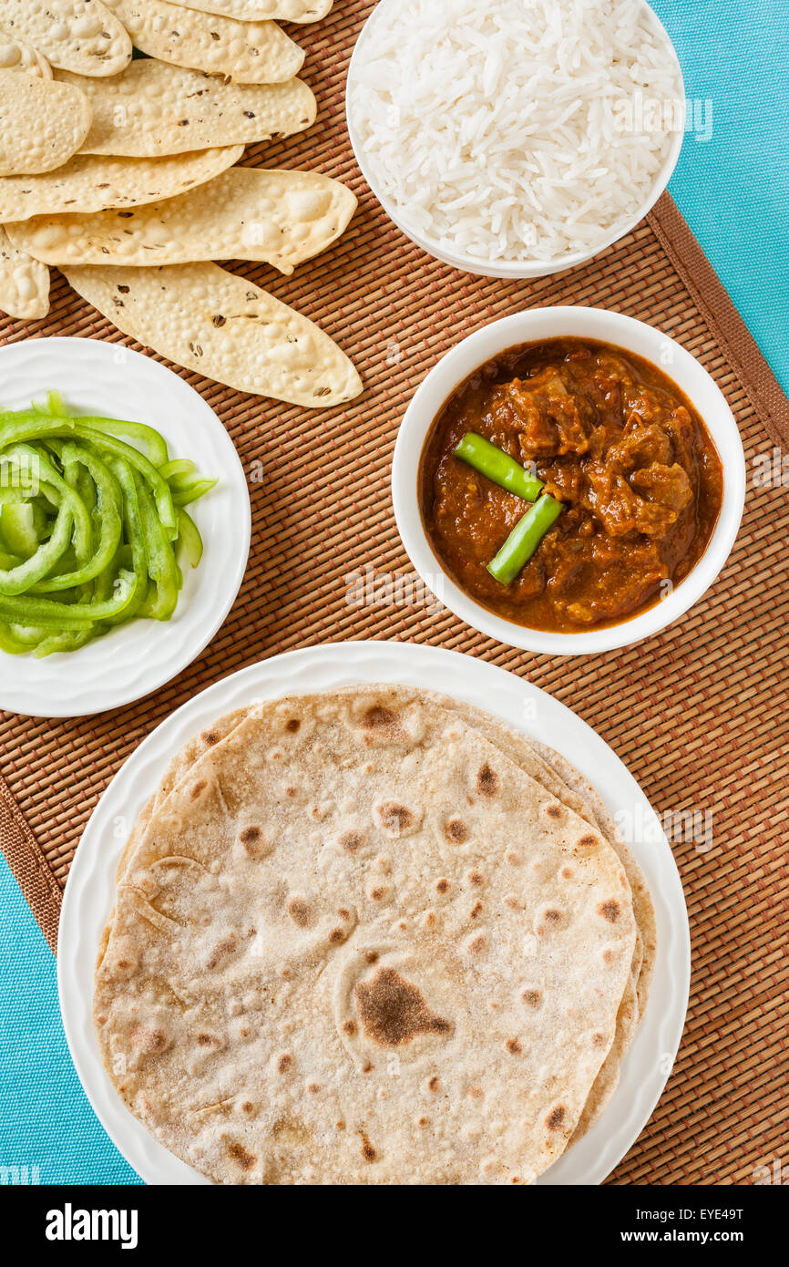 Overhead view of Indian mutton rogan josh meal with rice and chapati. This spicy hot Kashmiri dish uses red chilli. - Stock Image