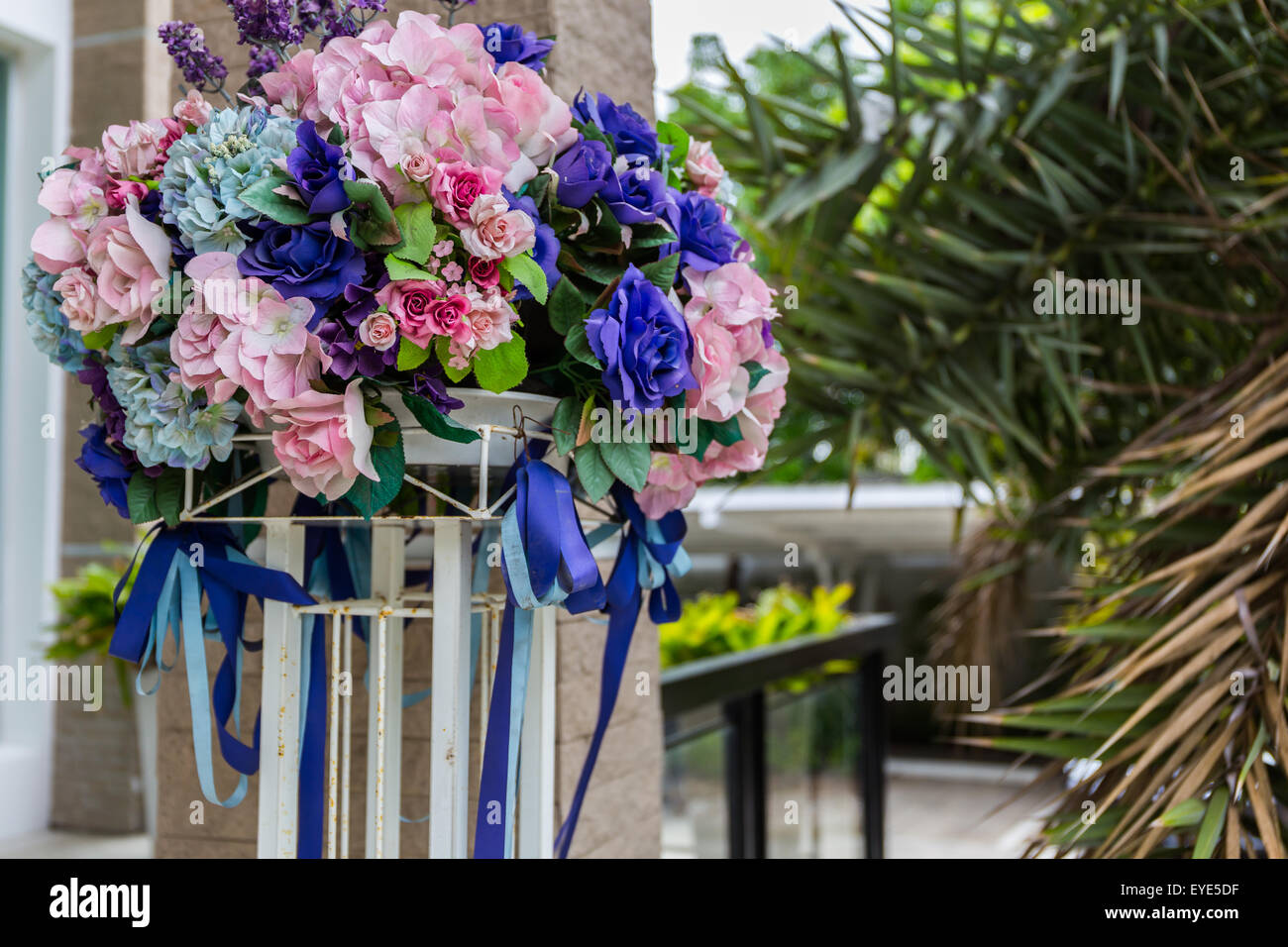 Colorful artificial flower bouquet in front of house. - Stock Image