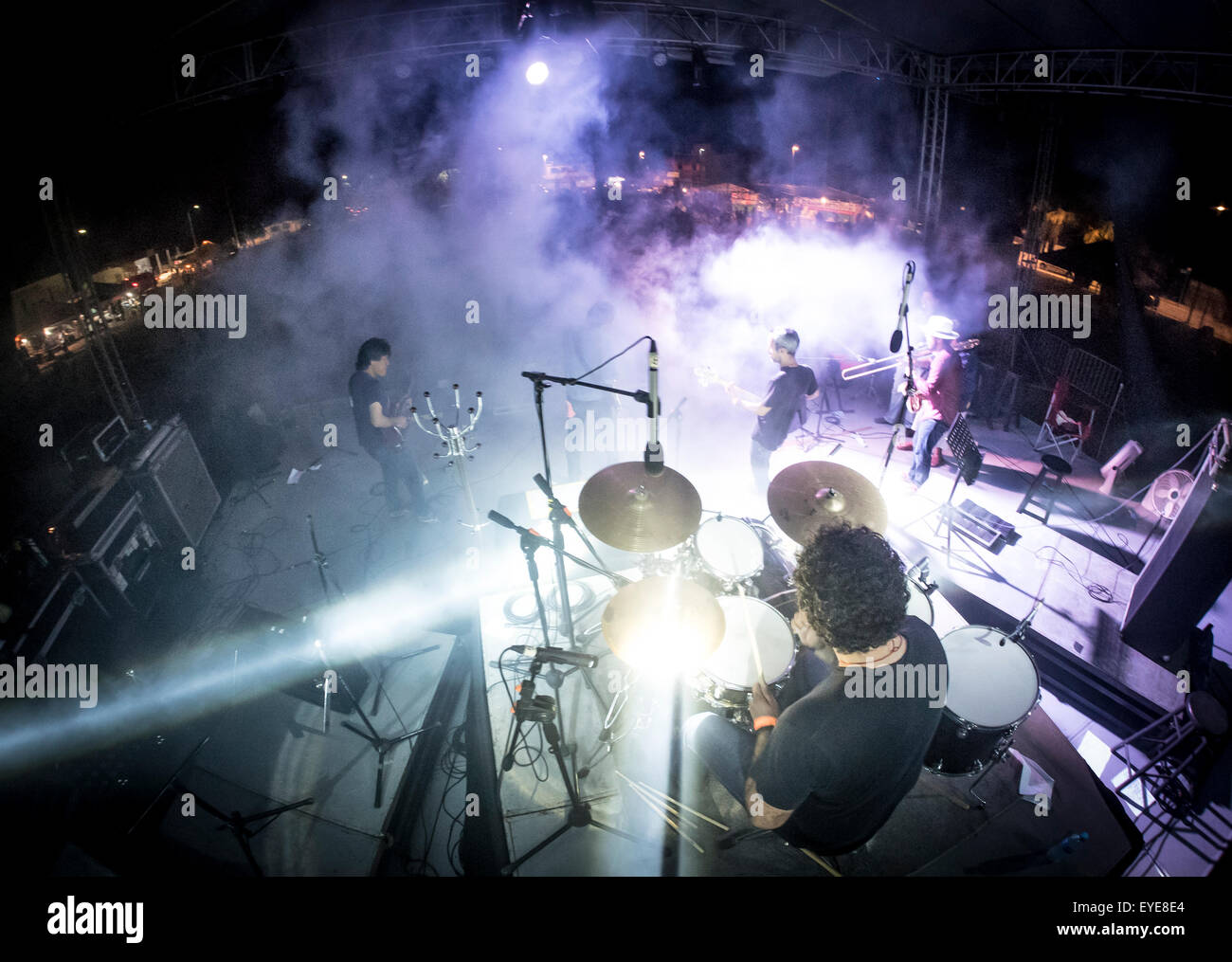 Rock band performing on outdoor stage with purple lights and fog as rock band performing on outdoor stage with purple lights and fog as seen from behind drummer workwithnaturefo