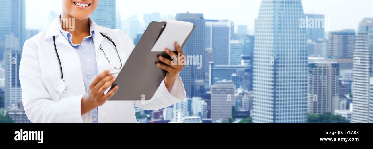 happy african female doctor with clipboard - Stock Image