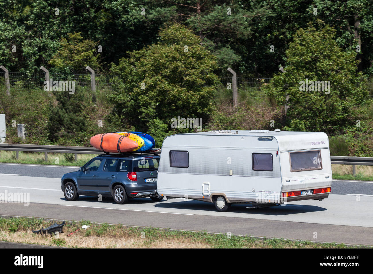 Skoda Yeti with an old caravan and kayaks on the roof - Stock Image