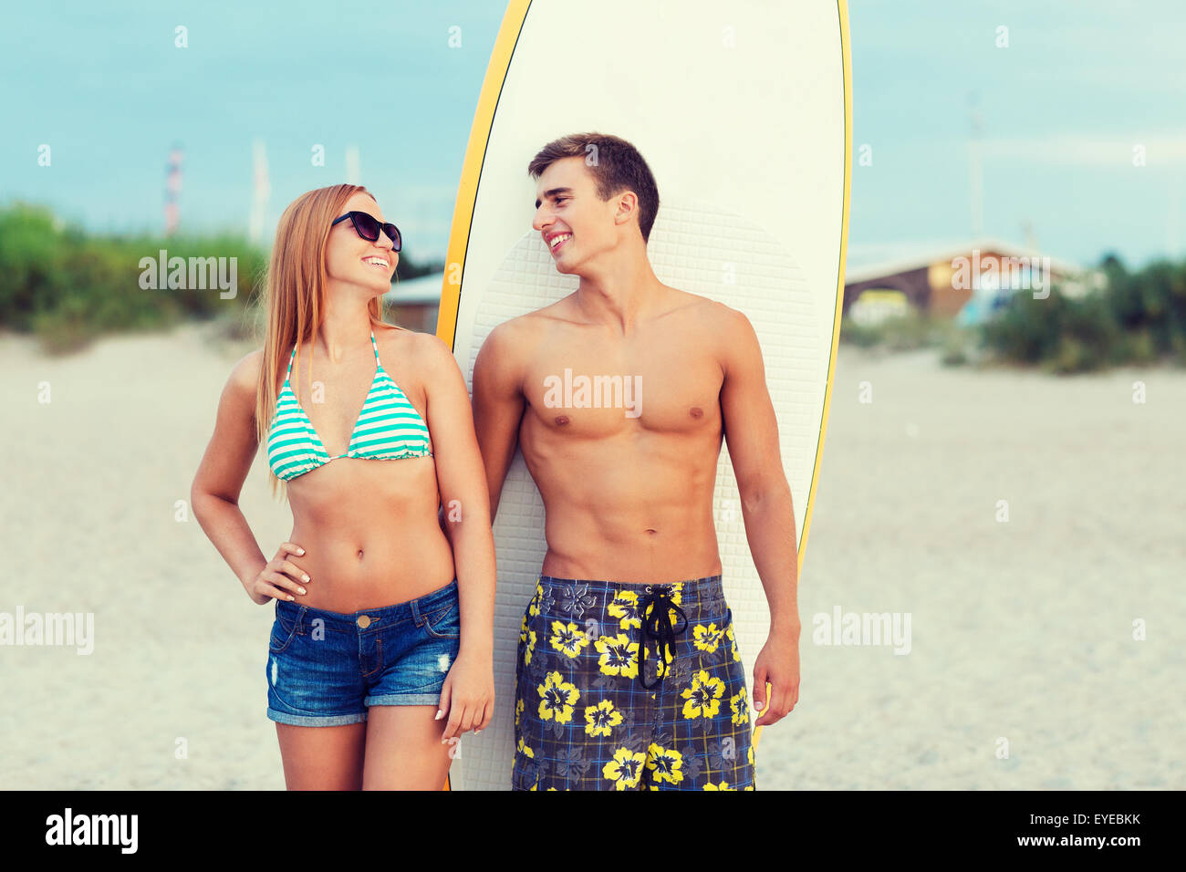 smiling couple in sunglasses with surfs on beach - Stock Image