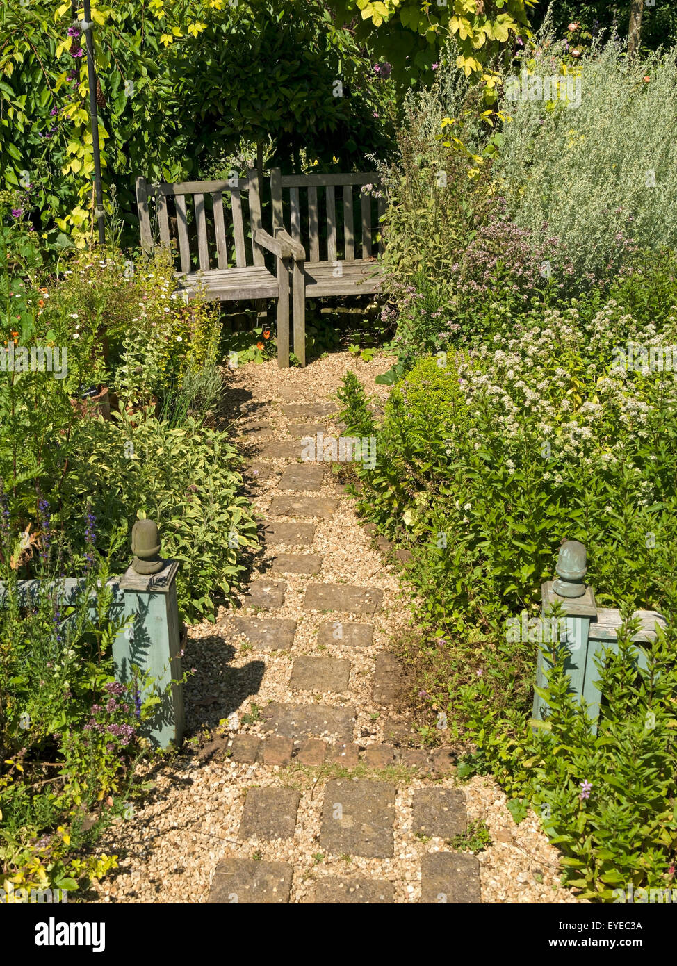 Small English cottage garden with paved and gravel path borders and