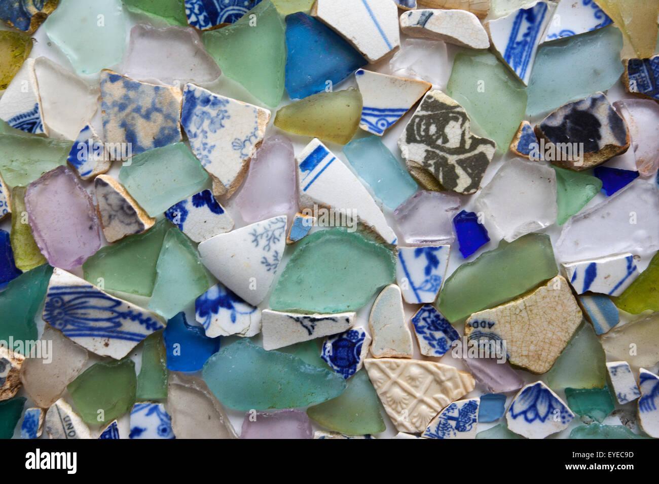Bits of coloured glass and broken crockery found when beachcombing in Scotland, UK - Stock Image