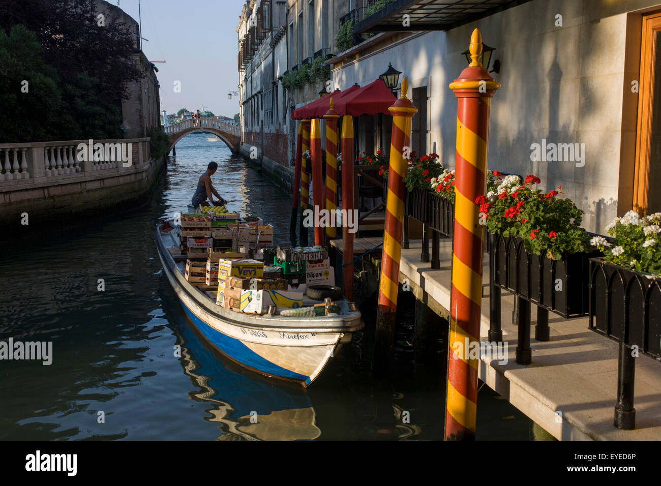 Delivery man reverses back from jetty, back on to Grand Canal after dropping off supplies in Venice, Italy. - Stock Image