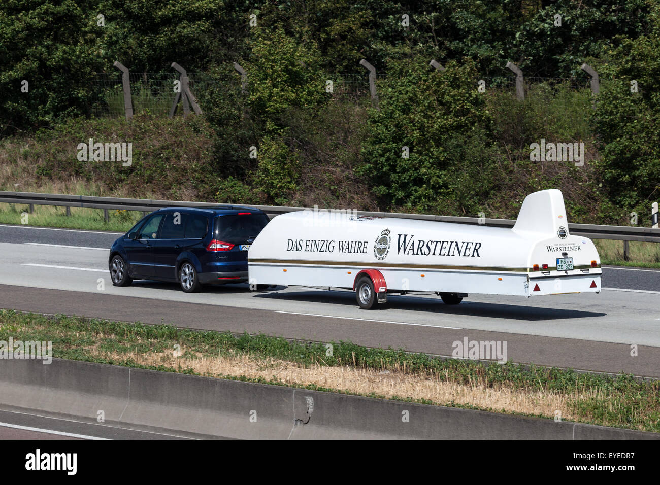Ford S-Max with a glider transport trailer on the highway - Stock Image