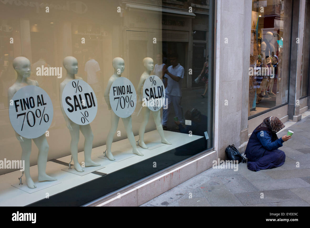 Retail mannequins advertising a 70% sale with a woman street beggar in the San Marco shopping district of Venice, - Stock Image