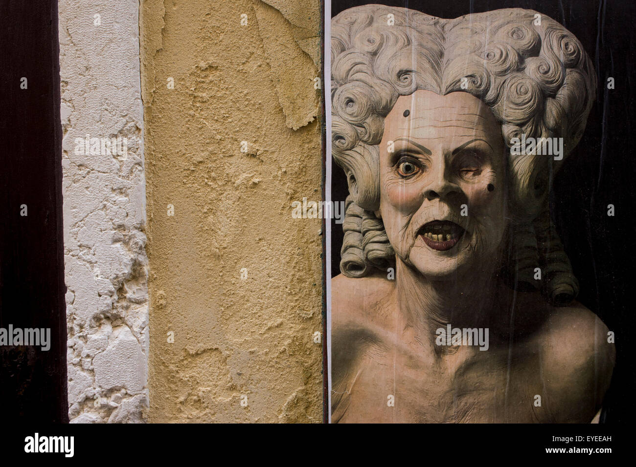 The texture of wall plaster echoed in the skin of a theatrical character in the San Marco shopping district of Venice, - Stock Image
