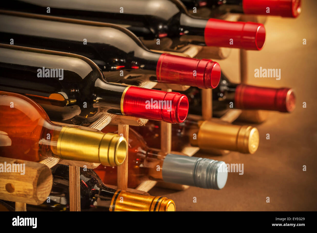 Wine bottles stacked on wooden racks shot with limited depth of field Stock Photo