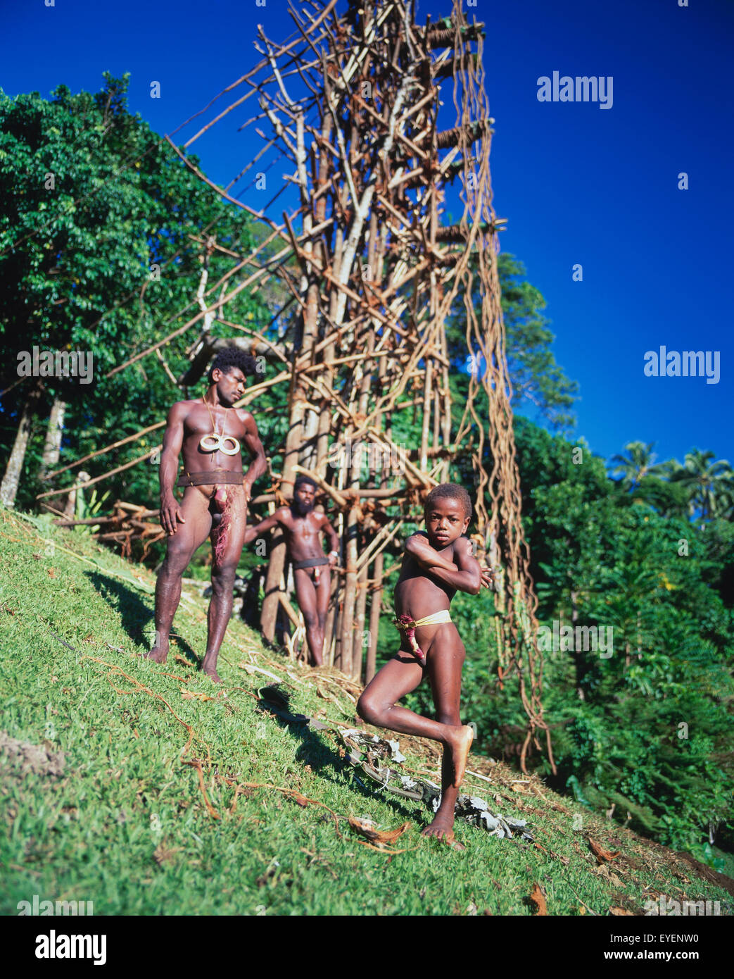 Young man and boy at the base of a land diving tower; Pentecost Island, Vanuatu - Stock Image
